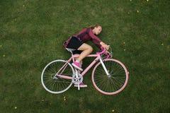 Punto di vista superiore della donna con la bicicletta sull'erba Fotografie Stock Libere da Diritti