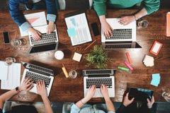 Punto di vista superiore della gente coworking che si siede insieme intorno alla tavola Riunione d'affari di giovani pantaloni a  Fotografia Stock Libera da Diritti