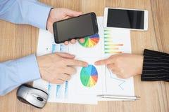 Punto di vista superiore della gente di affari che analizza rapporto e lettura di vendite fotografie stock