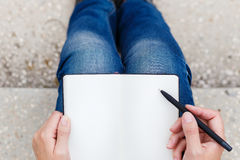 Punto di vista superiore della giovane donna che fa le note in taccuino Fotografie Stock