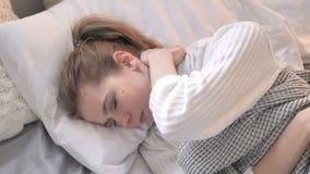 Punto di vista superiore della giovane donna con dolore al collo che si situa a letto archivi video