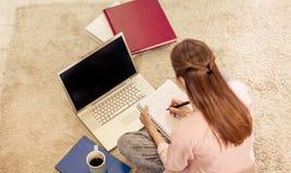 Punto di vista superiore della ragazza che si siede sulla scrittura del tappeto in taccuino Fotografie Stock