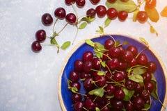 Punto di vista superiore delle ciliege in un piatto e su una tavola per produrre composta o succo fresco Fotografia Stock Libera da Diritti
