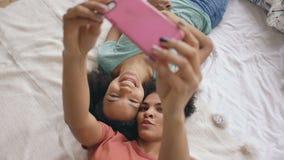 Punto di vista superiore delle ragazze divertenti allegre della corsa mista che fanno il ritratto del selfie sul letto in camera  video d archivio