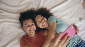 Punto di vista superiore delle sorelle divertenti allegre della corsa mista che fanno il ritratto del selfie sul letto in camera  archivi video