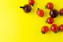 Punto di vista superiore delle verdure su fondo giallo luminoso Cipolle, pomodori freschi su fondo moderno immagine stock libera da diritti