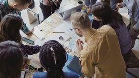 Punto di vista superiore di giovane gruppo che lavora al nuovo progetto Gruppo di gente della corsa mista che sta vicino alla tav video d archivio