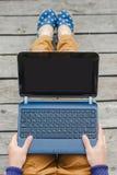 Punto di vista superiore di giovane ragazza dei pantaloni a vita bassa che per mezzo del computer portatile fotografie stock libere da diritti