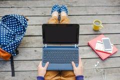 Punto di vista superiore di giovane ragazza dei pantaloni a vita bassa che per mezzo del computer portatile immagini stock libere da diritti