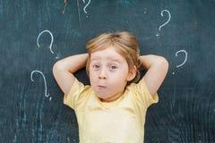 Punto di vista superiore di piccolo ragazzo biondo del bambino con il punto interrogativo sulla lavagna Concetto per confusione,  Immagine Stock Libera da Diritti