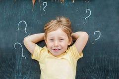 Punto di vista superiore di piccolo ragazzo biondo del bambino con il punto interrogativo sulla lavagna Concetto per confusione,  Fotografia Stock Libera da Diritti