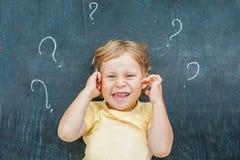 Punto di vista superiore di piccolo ragazzo biondo del bambino con il punto interrogativo sulla lavagna Concetto per confusione,  Fotografie Stock