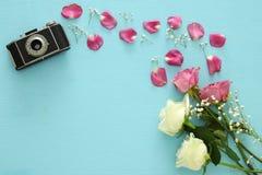 Punto di vista superiore di vecchie macchina fotografica e rose sopra la tavola di legno Immagine Stock Libera da Diritti