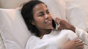 Punto di vista superiore di giovane donna africana che parla sul telefono a letto archivi video