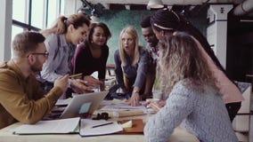 Punto di vista superiore di giovane gruppo che lavora al progetto architettonico Gruppo di gente della corsa mista che sta tavola stock footage