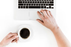 Punto di vista superiore parziale della persona che tiene tazza di caffè e che per mezzo del computer portatile isolato su bianco Immagini Stock Libere da Diritti