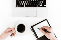 Punto di vista superiore parziale della persona che tiene tazza di caffè e che scrive sulla carta in bianco nel luogo di lavoro c Fotografia Stock