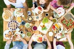 Punto di vista superiore di un gruppo di amici che si siedono ad un cibo di legno della tavola fotografia stock