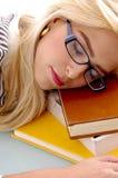 Punto di vista vicino della femmina che dorme sui libri Immagine Stock