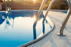 Punto di vista vicino della piscina moderna al tramonto all'hotel Luce solare in superficie Le vacanze estive, feste, si rilassan immagini stock libere da diritti
