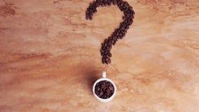 Punto interrogativo dei chicchi di caffè Un segno dai chicchi di caffè sulla tavola a foglie rampanti di marmo Tazza bianca con i stock footage