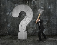 Punto interrogativo incrinato del martello della tenuta dell'uomo d'affari con mottl scuro Fotografia Stock