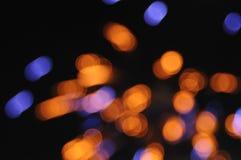Puntos anaranjados de estallido de los fuegos artificiales con el azul Foto de archivo libre de regalías