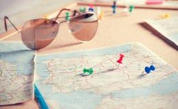 Puntos de destino del viaje en un mapa y las gafas de sol Imagenes de archivo