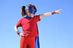 Puntos de la muchacha del super héroe hacia el cielo azul dramático fotografía de archivo