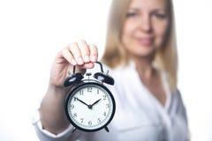Puntos de la mujer de negocios en ella reloj Oficina Manager Foto del estudio en un fondo blanco Imagen de archivo