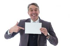 Puntos de mediana edad del hombre a la tarjeta en blanco Ejecutivo en traje en el fondo blanco fotografía de archivo
