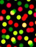 Puntos rojos y verdes en el papel pintado negro Fotografía de archivo libre de regalías