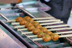 Puntura della palla della crocchetta di pesce da parte a parte con la griglia di bambù fotografie stock libere da diritti