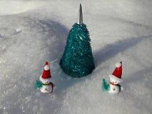 Pupazzi di neve vicino all'albero di Natale artificiale nella neve Fotografia Stock
