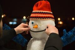 Pupazzo di neve alla notte Fabbricazione del pupazzo di neve fotografia stock