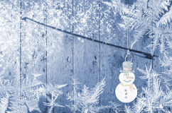 Pupazzo di neve allegato all'arco di violino, blu, fondo di legno Fiocchi di neve di orario invernale intorno Fotografie Stock Libere da Diritti