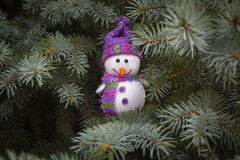 Pupazzo di neve allegro con una sciarpa che si nasconde vicino ad un albero di Natale Fotografia Stock Libera da Diritti
