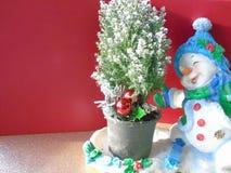 Pupazzo di neve allegro felice di Natale che pattina intorno ad un albero di natale fotografie stock libere da diritti