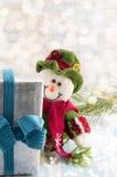 Pupazzo di neve che si nasconde dietro il regalo di Natale Fotografie Stock