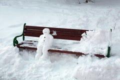 Pupazzo di neve che si siede sul banco Fotografia Stock Libera da Diritti