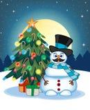 Pupazzo di neve con i baffi che portano un cappello e una sciarpa blu con l'albero di Natale e la luna piena al fondo di notte pe Fotografia Stock