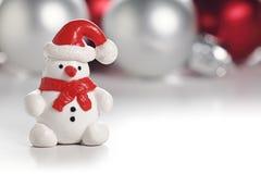 Pupazzo di neve con il cappello di Santa Il Babbo Natale su una slitta Immagini Stock