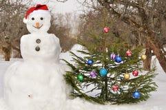 Pupazzo di neve con l'albero di Natale Immagine Stock