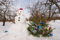 Pupazzo di neve con l'albero di Natale Fotografie Stock