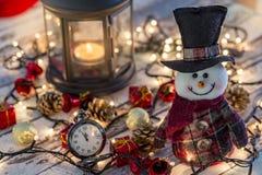 Pupazzo di neve con l'orologio da tasca, le decorazioni di natale e le luci immagine stock