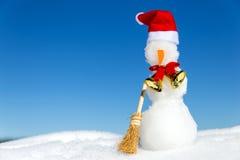 Pupazzo di neve con uno spiritello malevolo, una campana dorata e un'asta nella neve Fotografie Stock