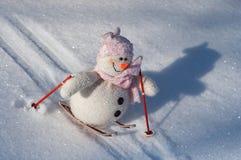 Pupazzo di neve del panno sugli sci giù un pendio con neve, Immagini Stock