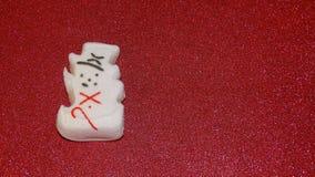Pupazzo di neve della caramella gommosa e molle con il fondo rosso di scintillio Fotografia Stock