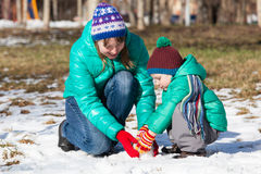 Pupazzo di neve della costruzione del figlio e della madre nell'inverno Fotografia Stock