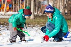 Pupazzo di neve della costruzione del figlio e della madre nell'inverno Fotografia Stock Libera da Diritti